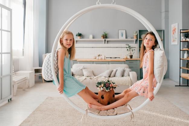 Dois filhos adoráveis em vestidos bonitos, sentado no balanço