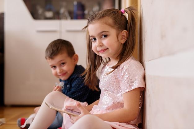 Dois filhos adoráveis estão brincando no chão da cozinha.