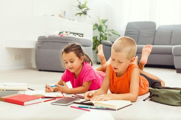 Dois filhos bonitos desenha no chão em casa