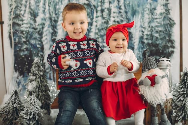 Dois filhos bonitos sentado em uma decoração de natal