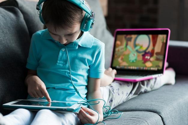 Dois filhos com laptop e tablet
