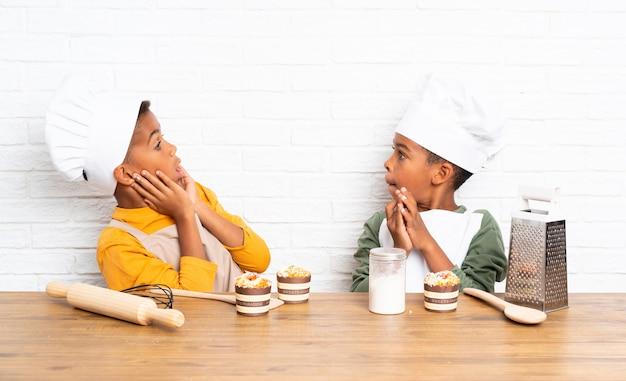 Dois filhos de irmãos afro-americanos vestidos como chef e fazendo gesto de surpresa