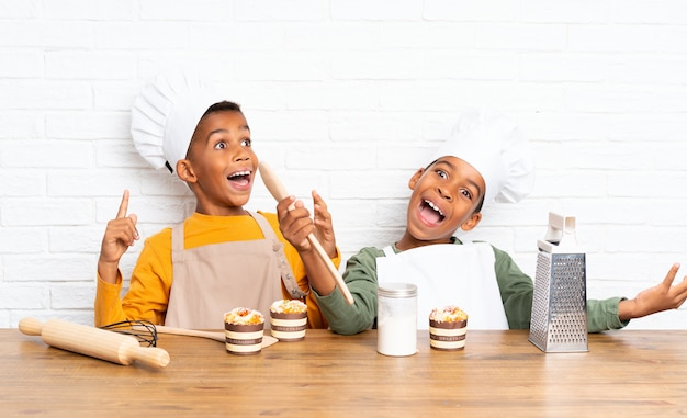 Dois filhos de irmãos afro-americanos vestidos como chef