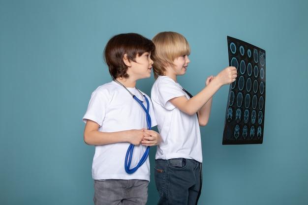 Dois filhos doce adorável fofo em jeans e camisetas brancas, assistindo o raio-x na mesa azul
