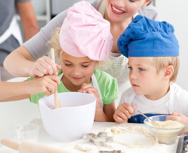 Dois filhos e sua mãe, mexendo uma preparação para biscoitos juntos
