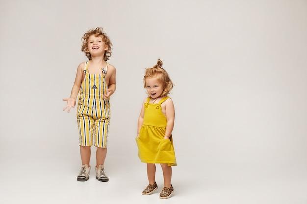 Dois filhos elegantes bonitos, menino e menina com roupas da moda verão posando em um fundo bege. isolado no comprimento total, com espaço de cópia