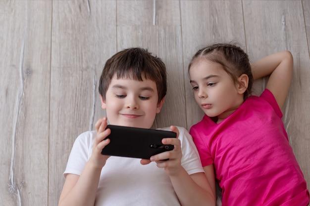 Dois filhos, irmão e irmã, estão deitados no chão e brincando em um smartphone