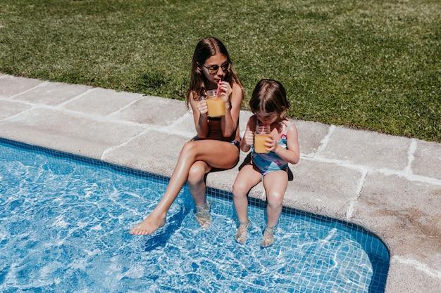 Dois filhos linda irmã na piscina bebendo suco de laranja saudável e se divertindo ao ar livre. conceito de verão e estilo de vida