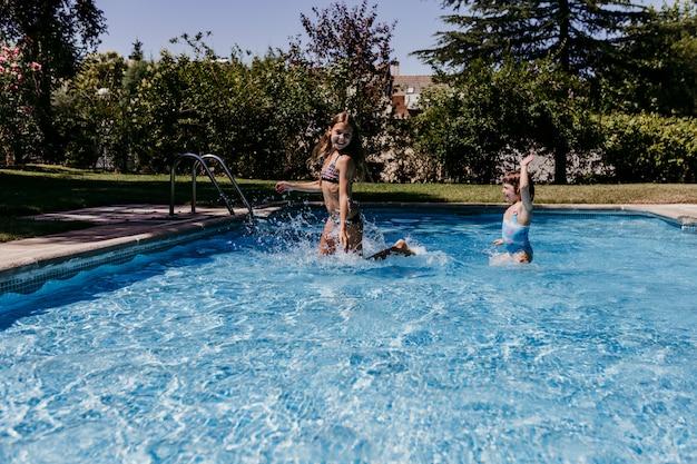 Dois filhos linda irmã na piscina brincando, correndo e se divertindo ao ar livre. conceito de verão e estilo de vida