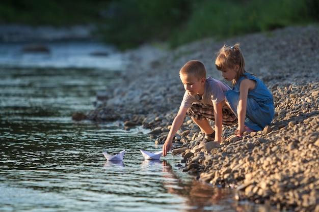 Dois filhos loiros bonitos, menino e menina na margem do rio enviando em barcos de papel branco de água