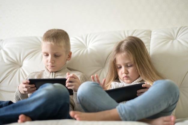 Dois filhos pequenos, menino e menina, segurando o tablet e assistindo desenhos animados em casa, sentados no sofá