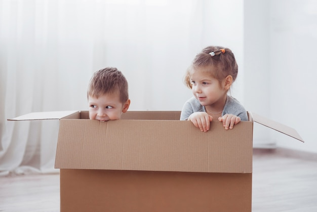 Dois filhos um menino e uma menina brincando em caixas de papelão. foto do conceito. as crianças se divertem.