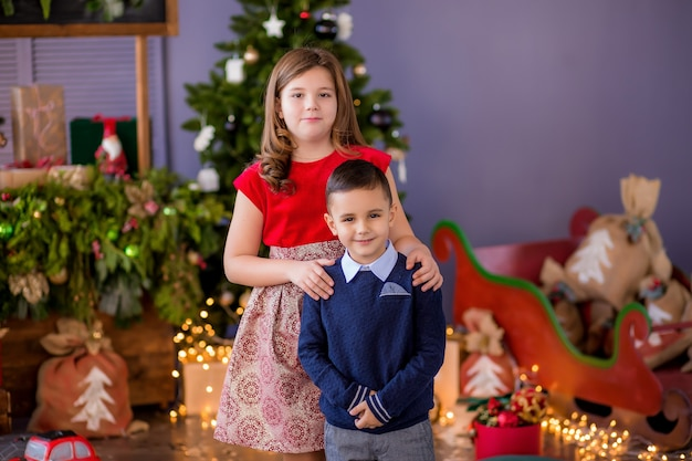 Dois filhos, uma menina e um menino perto de uma árvore de natal