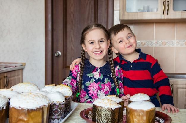 Dois filhos, uma menina e um menino, um irmão e uma irmã, criam um bolo de páscoa.