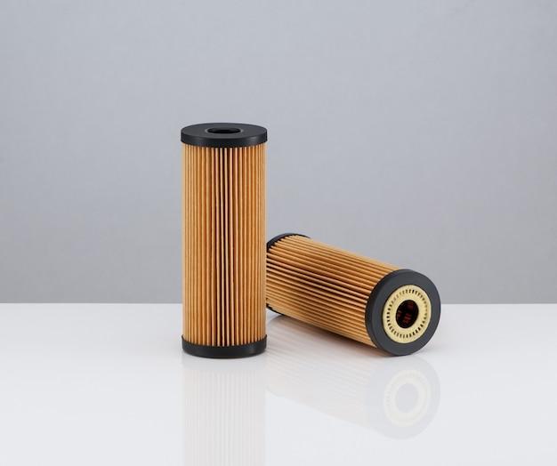 Dois filtros automotivos de forma cilíndrica de cor laranja em um fundo branco com reflexo