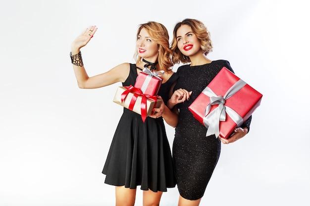 Dois fofa celebrando mulher segurando grandes caixas de presente de ano novo. rostos de surpresa. usando um elegante vestido preto.