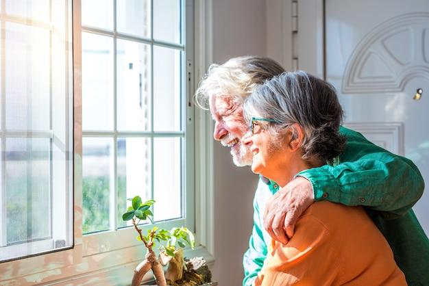 Dois fofos velhos e maduros ou idosos se divertindo juntos em casa, olhando para fora de sua casa, sorrindo e rindo