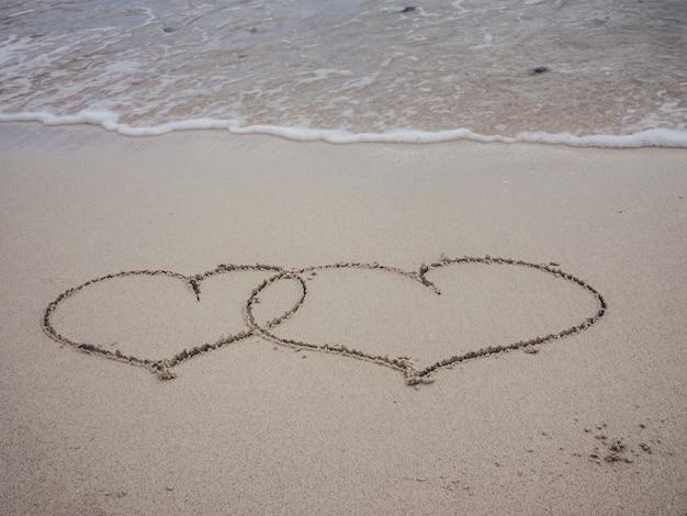 Dois forma coração escrevendo na praia de areia com ondas oceano