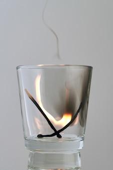 Dois fósforos carbonizados queimam em um vidro transparente