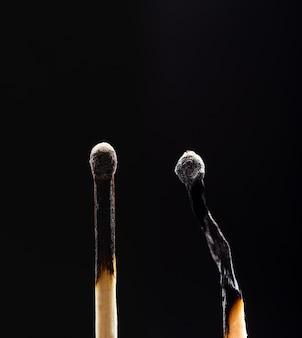 Dois fósforos de madeira queimados