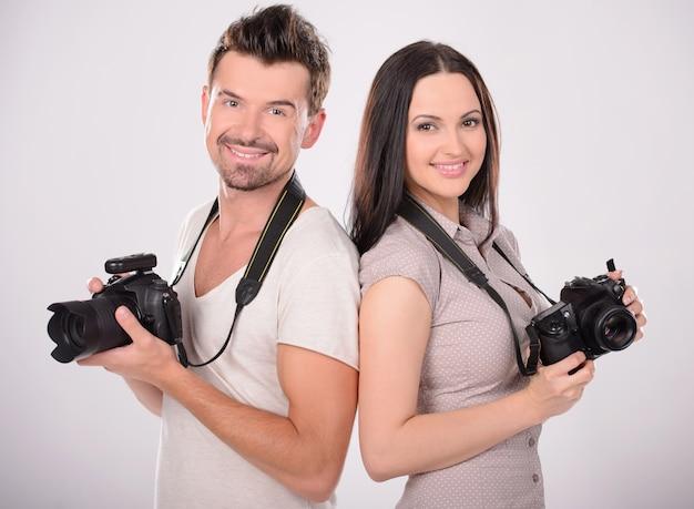 Dois fotógrafos alegres segurando câmeras.