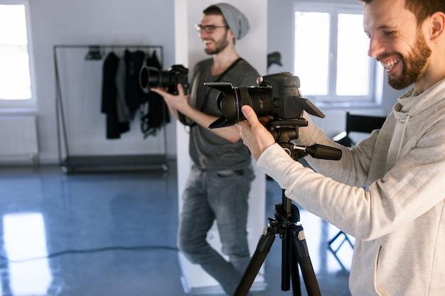 Dois fotógrafos profissionais risonhos tirando fotos em estúdio