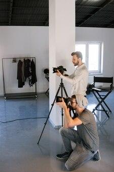 Dois fotógrafos tirando fotos em estúdio