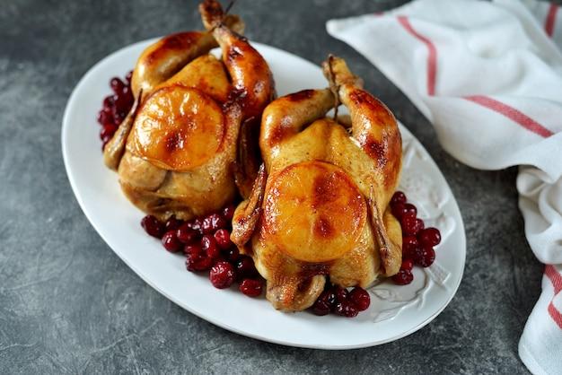 Dois frangos inteiros assados com cranberries e rodelas de laranja