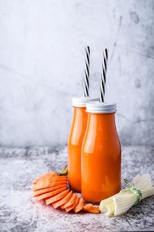 Dois frasco de vidro com cenoura e aipo batido na mesa