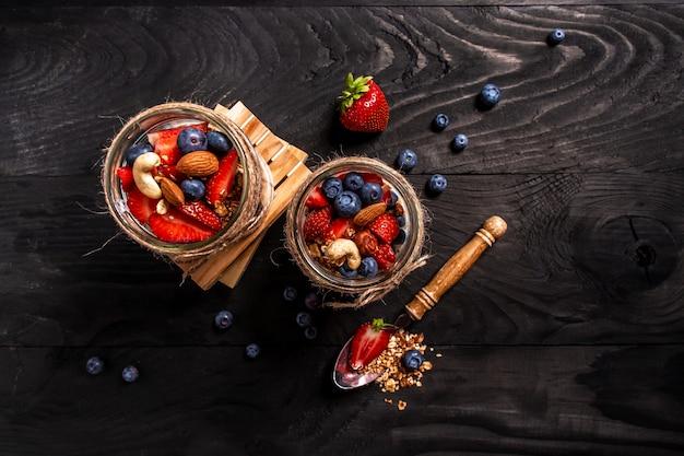 Dois frascos com saborosos parfaits feitos de granola, frutas, nozes e iogurte