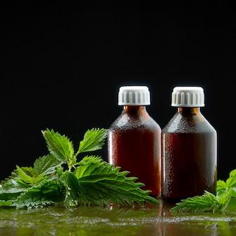 Dois frascos com uma infusão médica de uma decocção de urtiga com folhas de urtiga