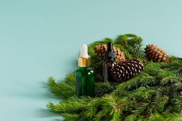 Dois frascos conta-gotas de óleo essencial e ramos de abeto. conceito de aromaterapia e spa de natal.
