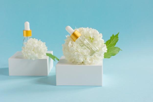 Dois frascos conta-gotas de vidro para uso médico e cosmético e flores brancas tenras sobre um fundo azul claro. cuidados com a pele e conceito de spa.