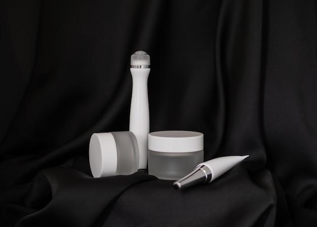 Dois frascos de cosméticos, um dos quais deitado e o outro de pé, ao lado deles sobre um fundo de seda preta está um tubo cosmético e um spray cosmético