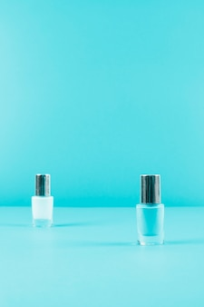 Dois frascos de esmalte sobre fundo azul, com espaço de cópia para escrever o texto
