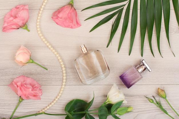 Dois frascos de perfume, miçangas em um cordão, flores brancas e rosa, folhas verdes sobre fundo de madeira. cosméticos woomen. vista do topo.