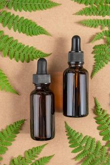 Dois frascos de vidro marrom com soro e folhas verdes de samambaia na superfície bege
