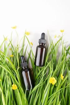 Dois frascos de vidro marrom com soro, óleo essencial de colágeno ou outro produto cosmético entre a grama