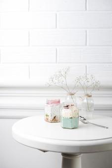 Dois frascos de vidro smoothies com colher na mesa contra parede branca