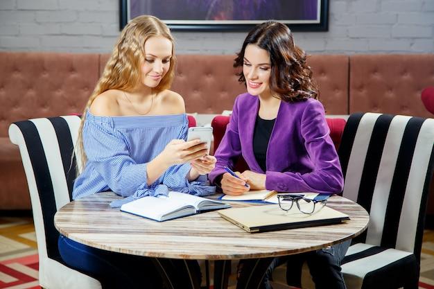 Dois freelancers estão discutindo novos projetos enquanto estão sentados em um café com dispositivos eletrônicos.