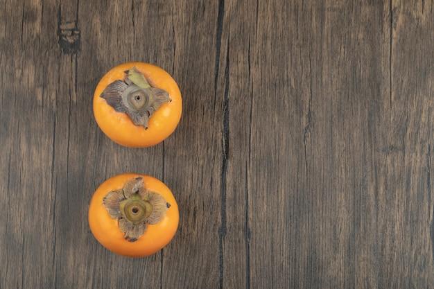 Dois frutos maduros de caqui colocados em superfície de madeira