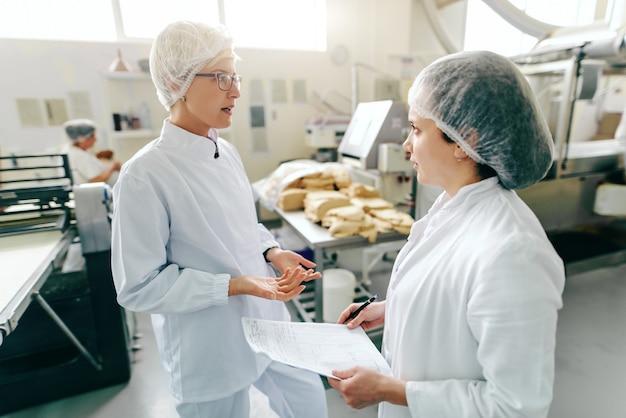 Dois funcionários caucasianos femininos falando sobre trabalho em pé na fábrica de alimentos. um deles segurando a papelada. em máquinas de segundo plano.