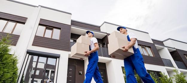 Dois funcionários da empresa de mudanças descarregando as caixas na casa de novos clientes