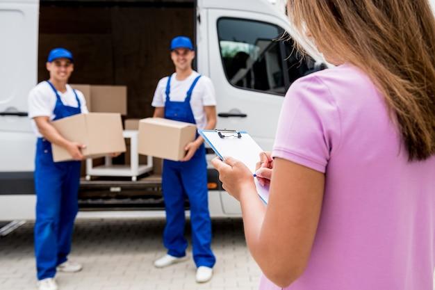 Dois funcionários da empresa de mudanças descarregando caixas do microônibus para a casa dos clientes
