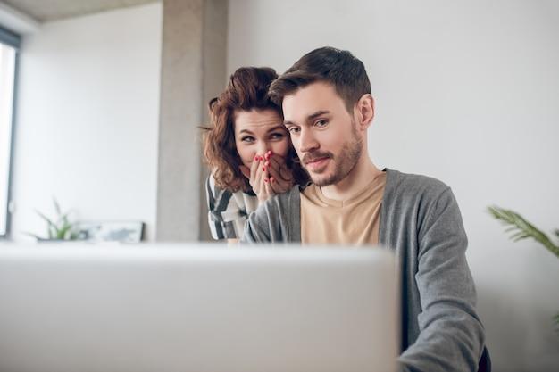 Dois funcionários de escritório surpresos lendo uma mensagem de e-mail