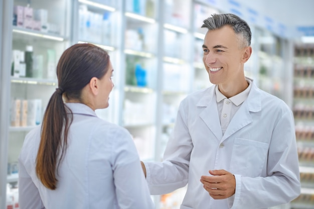 Dois funcionários de farmácia conversando alegremente no trabalho