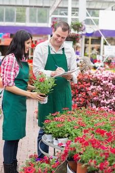 Dois funcionários do centro de jardinagem fazem anotações