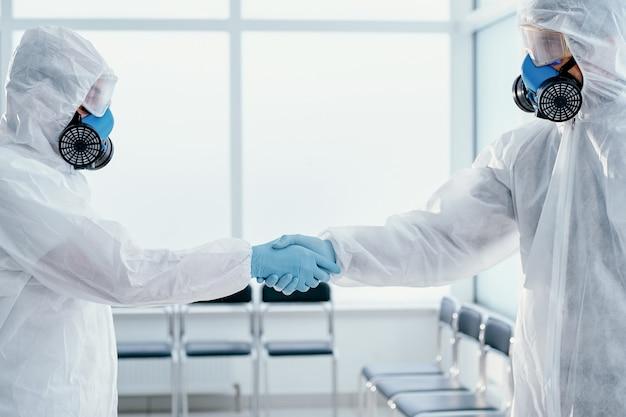 Dois funcionários do laboratório em trajes de proteção apertando as mãos um do outro