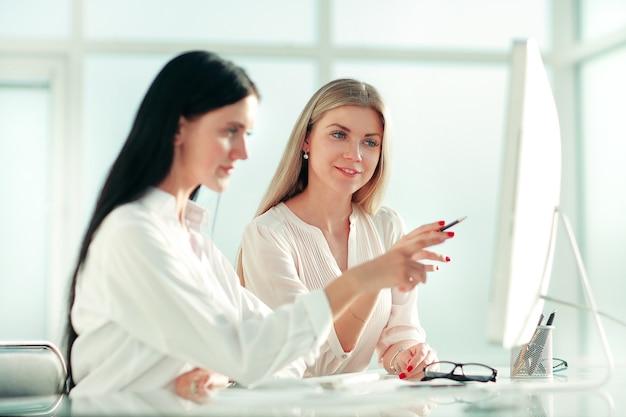 Dois funcionários estão discutindo algo sentados à mesa do escritório