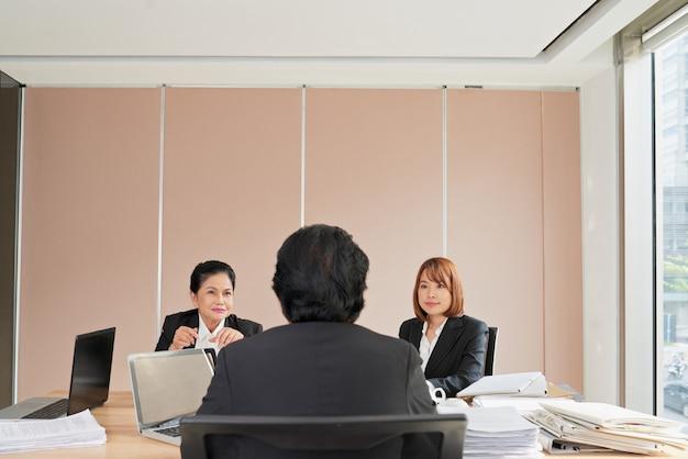 Dois funcionários subordinados se reportando ao gerente de uma empresa